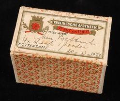 """Rechthoekig kartonnen pillendoosje """"Kralingse Apotheek Dr. A.H.C. Van Senus, Rotterdam"""" met handgeschreven tekst."""