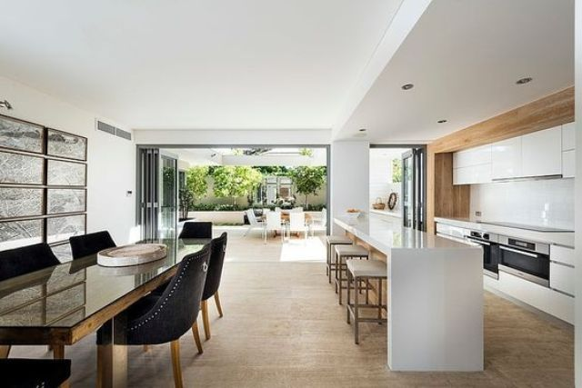 minimalist white kitchen with warm woods and a dining space with black chairs for a contrast
