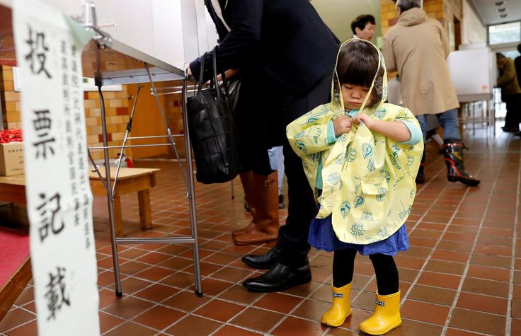 A girl stands next to her father filling out his ballot for a national election at a polling station in Tokyo