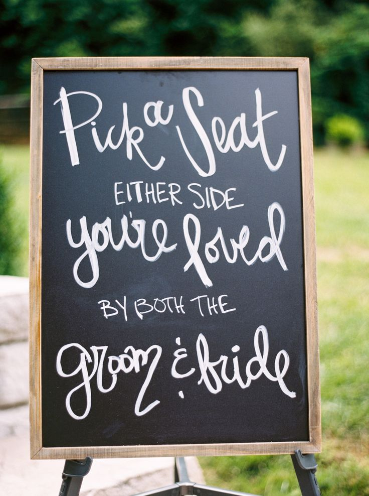 """Wedding ceremony signage, black chalkboard sign, wooden frame, """"Pick a seat either side you're loved by both the groom & bride"""" // JoPhoto"""