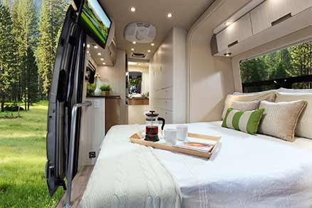 Leisure Travel Vans - Free Spirit SS. This shows the van with the slide in the out position and the bed unfolded. Note how coordinating colors are used to define separate areas. The galley on the left has walnut cabinets below and above, while the storage cabinets on the right are another color. The bathroom counter has a horizontal band of walnut to make it stand out, since bathroom counters are very rare in a Class B. Unfortunately, this model is no longer being made.