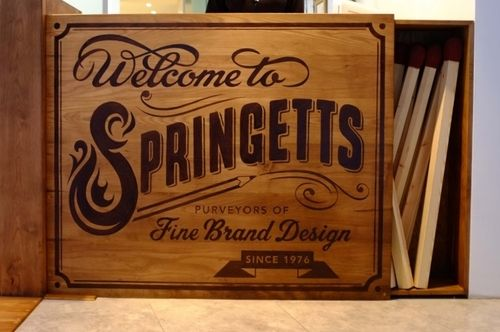 """Welcome to Springettes – Hand painted on a huge wooden """"box of matches"""" reception desk by Alison Carmichael."""