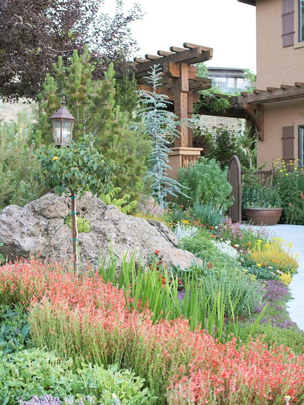 Sch ner garten mit gr nen pflanzen einer lampe und steinen for Gartengestaltung mit pflanzen