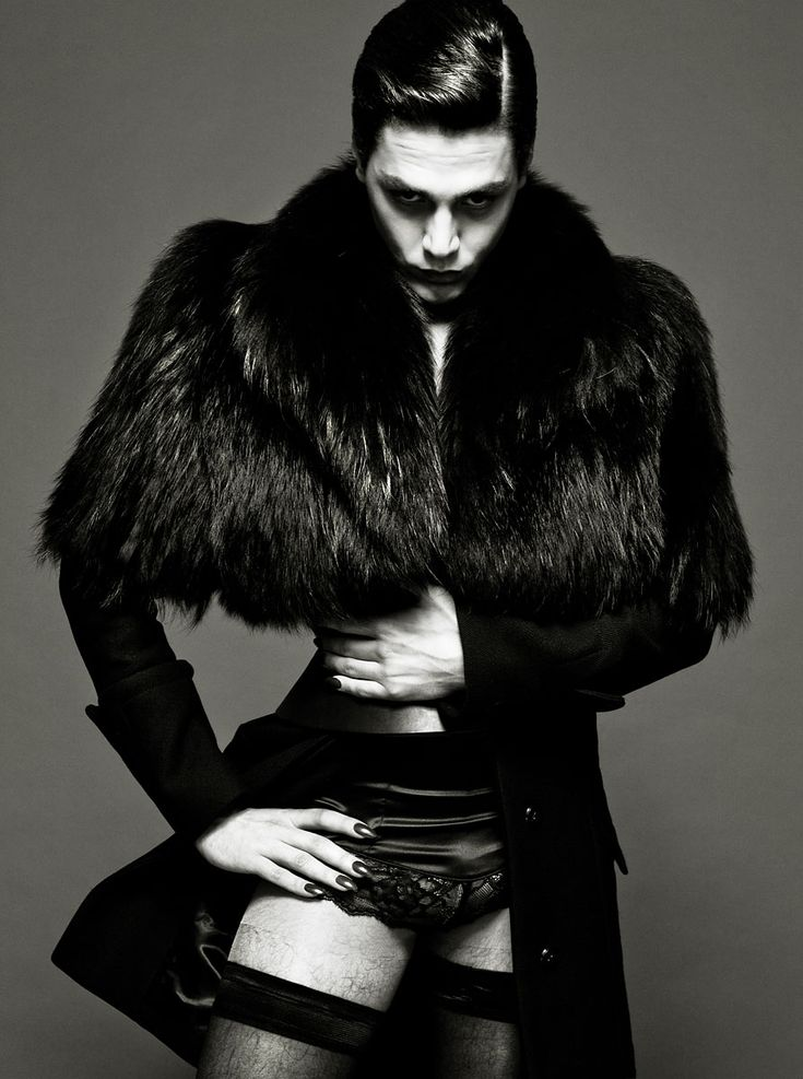 Male wearing black long sleeve jacket with fur overlay, satin underwear, and mesh thigh highs