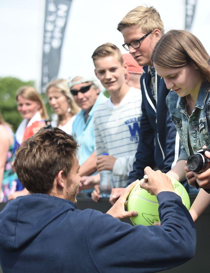 De winnaar van het voorbereidingstoernooi op Wimbledon, Topshelf Open, verblijd hier een fan met zijn handtekening na zijn gewonnen finale.