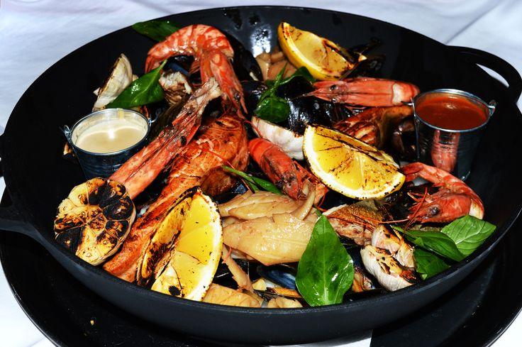 Огромная рыбная сковорода для большой компании (тигровые креветки, кальмары, ставрида, черноморские мидии, филе скумбрии, обжаренные на гриле, подается со спаржевой фасолью и соусами)