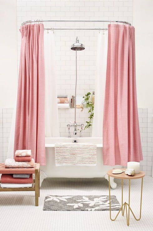 White and pink bathroom features a claw foot tub accented with two pink shower curtains, Shower Curtain Threshold Solid Pink, on oval shower rail mounted on subway tiled walls fitted with vintage style rain shower head over a built-in shelf filled with towels and bath accessories. Feminine, girly bathroom boasts a vintage clawfoot tub draped in a Threshold Rug Multi Coral, alongside an additional bath mat, Threshold Rug Heathered Floral, as well as a pink herringbone bench, Bench Threshol