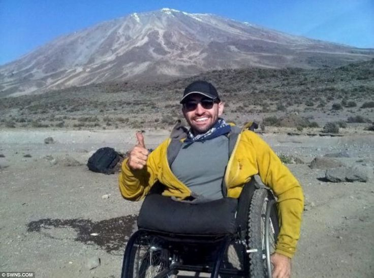 The brave climber grins as he reaches the foot of Kilimanjaro - ahead of the final trek to the top - AMAZING!