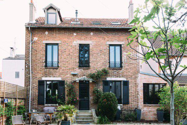 La maison en brique, construite au début du XXème siècle, est restée dans son jus avec sa porte, son entrée, ses garde-corps de fenêtres et ses volets en bois d'origine au charme d'antan, simplement repeints. Dans l'extension, à droite, se situe le nouveau salon.