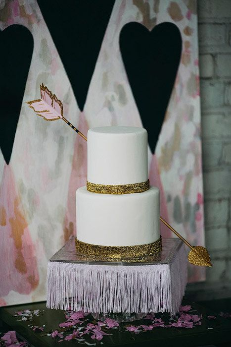This golden and white two tiered wedding cake has a very romantic twist to it! Shot by Cupid's arrow, you can't help but love this cake!