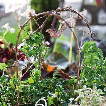 Jeremie | Antiqued vine arbor with tiny metal bird ornament.