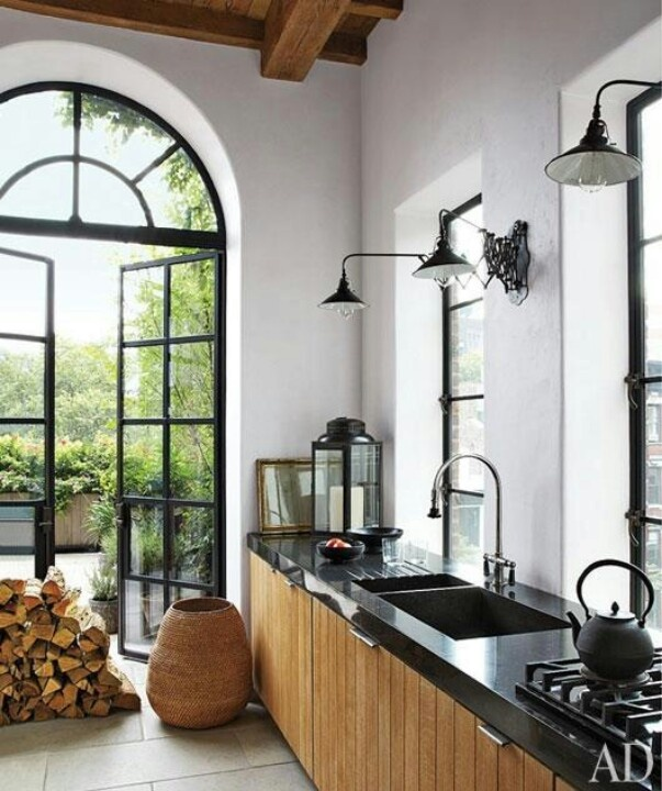 Kitchen with white walls, black countertops, wood paneled cabinets, and steel-frame door