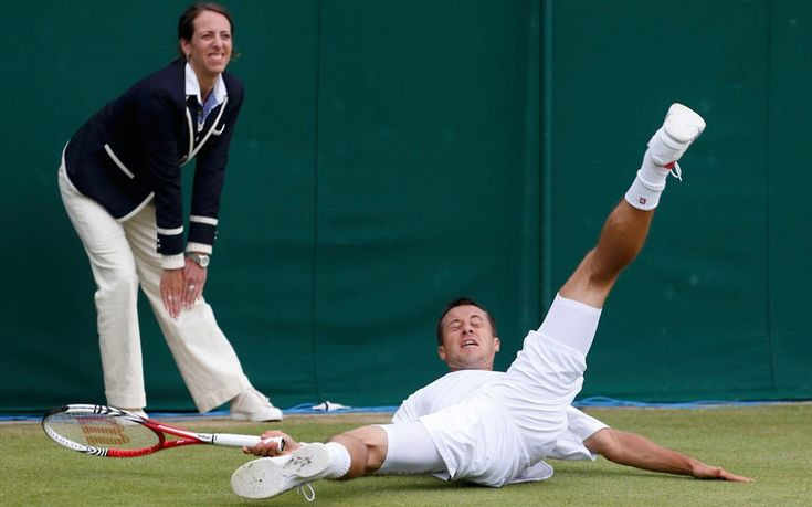 Philipp Kohlschreiber of Germany slips during his men's singles tennis match against Brian Baker of the US at the Wimbledon tennis championships.