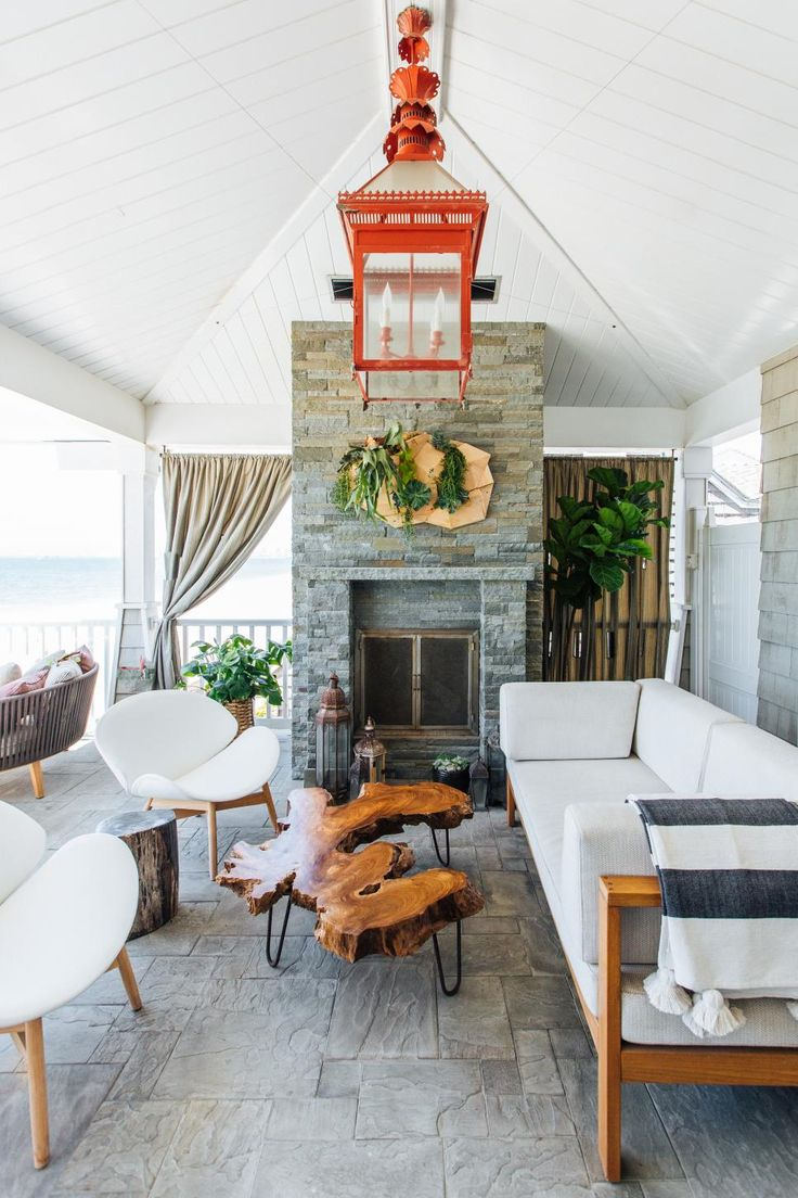 Midcentury modern furniture pairs with Cape Cod-style architecture to create this stylish yet classic outdoor living space. A bold red-orange lantern adds a vibrant splash of color and personality to the space.