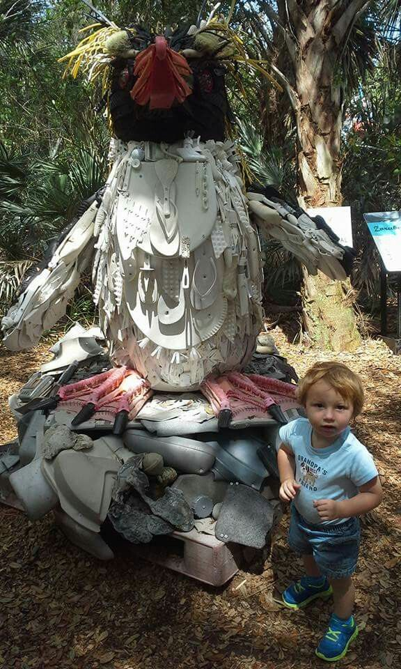 Posing with a penguin made from trash pulled from the ocean at the brevard zoo with gma amd gpa.