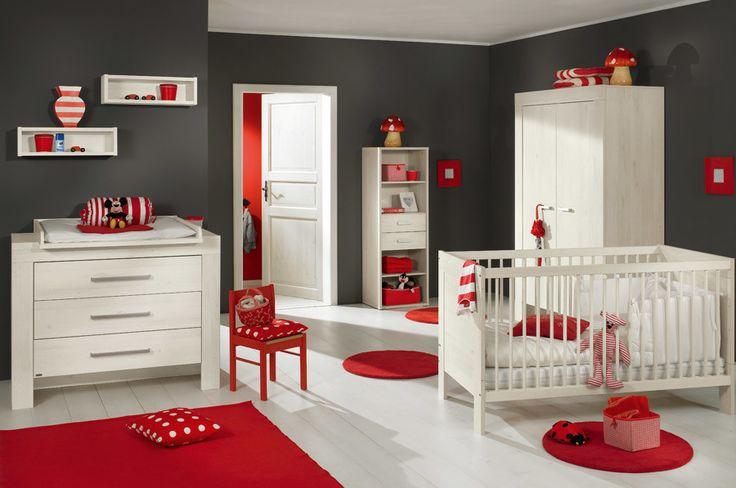 Hier dominieren nebem Weiß, Rot und Anthrazit: Babybett und Kommode stehen vor der dunklen Wand; das Rot kontrastiert zu beidem.