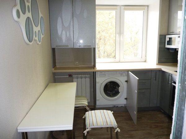 Кухня со встроенной стиральной машиной и маленьким столиком