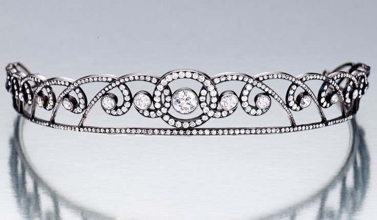 DIAMOND TIARA, CIRCA 1910, Designed as a graduated series of circular-cut diamonds, embellished by circular-cut diamond-set scrolls, the diamonds together weighing approximately 6.00 carats, mounted in platinum, French assay marks, two tiny diamonds deficient