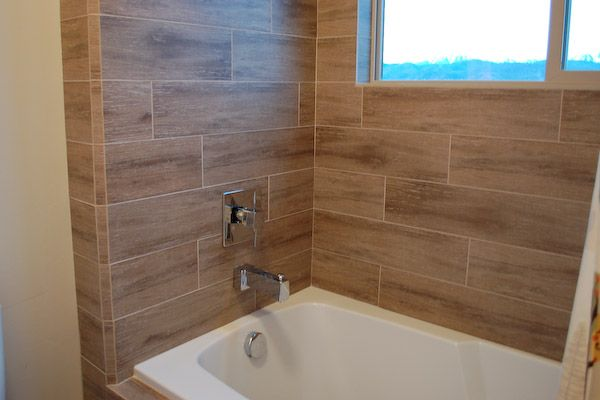 wood textured tiles on tub surround bathroom remodel