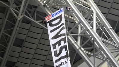 Police arrested three protesters after they rappelled into Vikings stadium to unfurl a banner calling for US Bank to divest financial interests in the Dakota Access Pipel