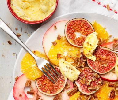 En fräsch fruktsallad som passar perfekt på julens dessertbord. Apelsiner, fikon, äpplen och pecannötter toppas av en mjuk och krämig saffransmascarpone.