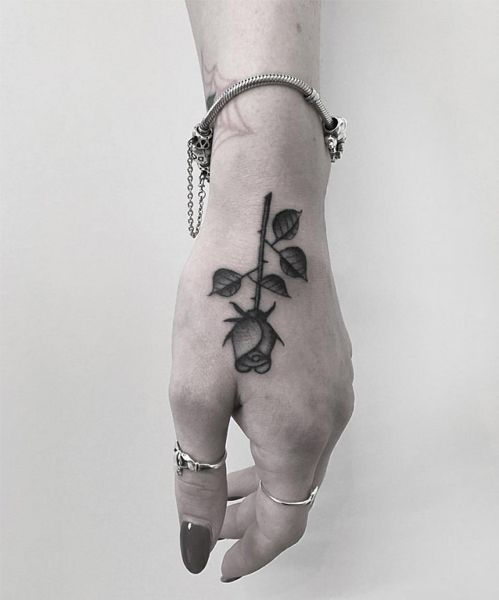Beautifully Placed Rose and Branch Tattoo Design on Hand