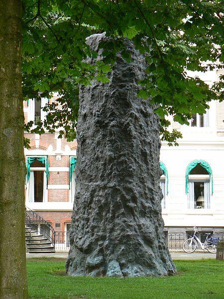 """""""Der Baum"""" aan de Heresingel, Groningen - 2007 - Het werk van Armando heeft altijd met de Tweede Wereldoorlog te maken, dus het was een logische stap hem te vragen een monument te ontwerpen ter nagedachtenis aan de, vlak voor de bevrijding door de Duitsers gefusilleerde, Groninger drukker/kunstenaar Hendrik Nicolaas Werkman. Het is een indrukwekkend beeld geworden, op een mooie plek. Een verkoolde boomstam aan een lege groene singel."""