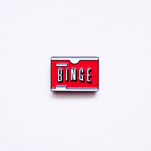 This is a pre-sale for our Binge Pin design: A symbol of the guilty pleasure that unites us all.<b>Shipping:</b> All pre-sale items are guaranteed to ship within the month of January 2016. Worldwide shipping available.<b>Status:</b> Safe<b>Specs:</b>- Soft Enamel- 1 inch- Black metal backing- Rubber clutch