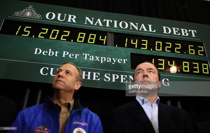 Supporters of republican presidential candidate former Massachusetts Gov. Mitt Romney stand next to a national debt clock during a rally at Exeter High School on January 8, 2012 in Exeter, New Hampshire. With days to go before the New Hampshire primary, Mitt Romney is making a final campaign swing through the state.