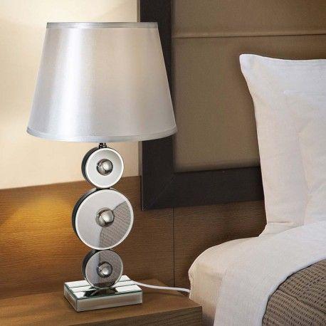 Lámpara de sobremesa Lion con bombilla LED de 10 W. El diseño de esta lámpara está compuesto por tres formas circulares de cristal en distinto tamaño fabricadas sobre base de DM lacada negra. Una lámpara ideal para iluminar con modernidad tu dormitorio.