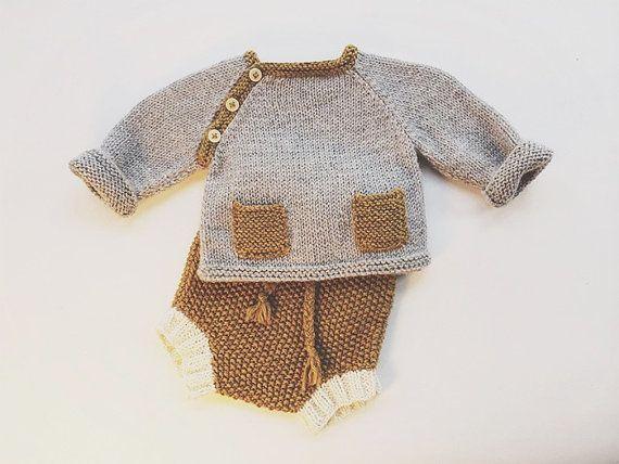 Había tejido a mano suéter de bebé de brezo del gris con dos bolsillos delanteros. Toques de color mostaza contraste amarilla en una puntada