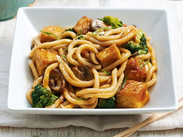 Japanese udon noodles, which cook in a matter of minutes, soak up all of the slightly spicy umami-rich sauce in this stir-fry. Cubes of golden tofu make the meat-free supper substantial.