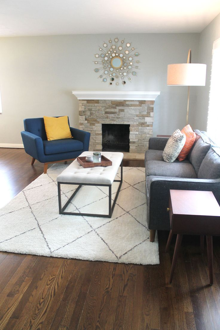 Midcentury modern living room with blue gray walls, grey couch, blue chair, brass lighting and mirror, white ottoman coffee table, white and grey rug, arc floor lamp, and accent pillows. Silver strand Sherwin Williams paint. West elm lamp and Hamilton sofa