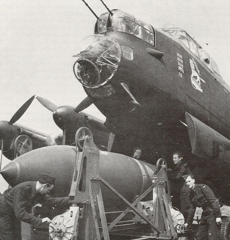 """A Royal Air Force Avro Lancaster being """"bombed up"""" with a 12,000 pound Tallboy earth-penetrating bomb."""