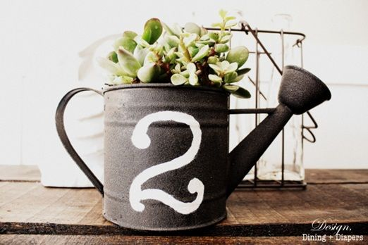 This is a cute idea and could be placed out in your garden afterwards as an unusual planter. Car boots and online auctions would be a good place to search for old style metal watering cans and they don't have to be in mint condition to look great. You can leave them as is or sand them down and paint them. Watering can table centrepiece