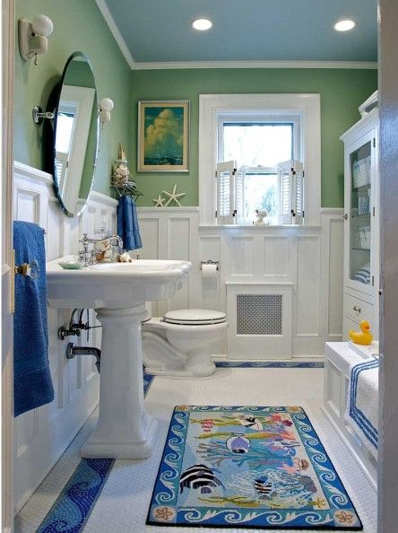 The sanitary white bath edges toward cottage style with a wood wainscot and whimsical wave border in the floor tile.