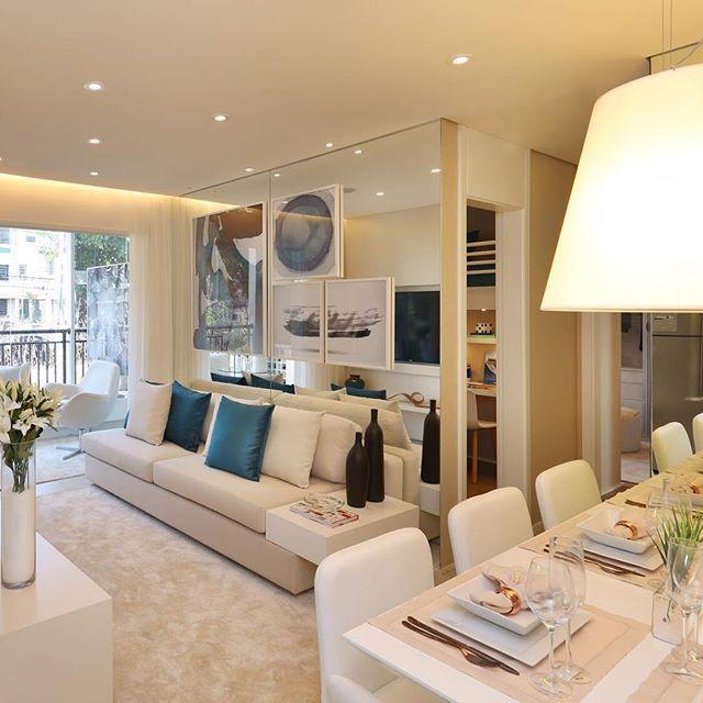 Parede espelhada atrás do sofá amplia o ambiente, e a composição de qu...