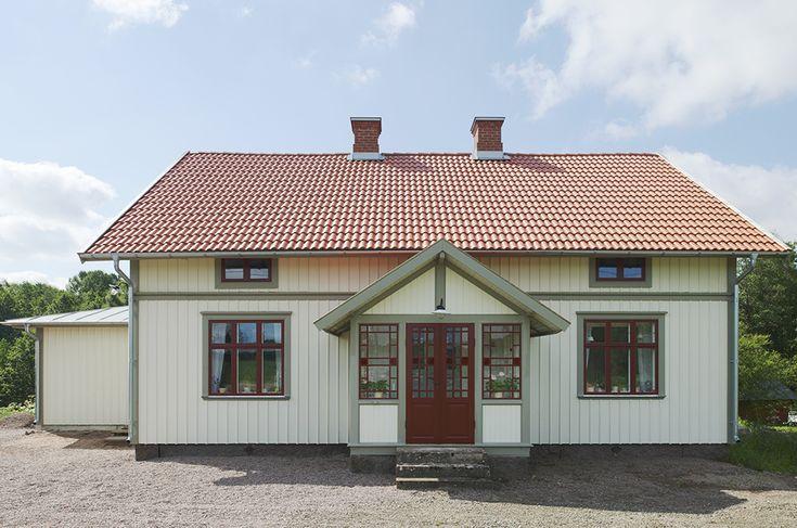 Naturvitt hus. Rött tak. Gröna och röda detaljer. Röd dörr.
