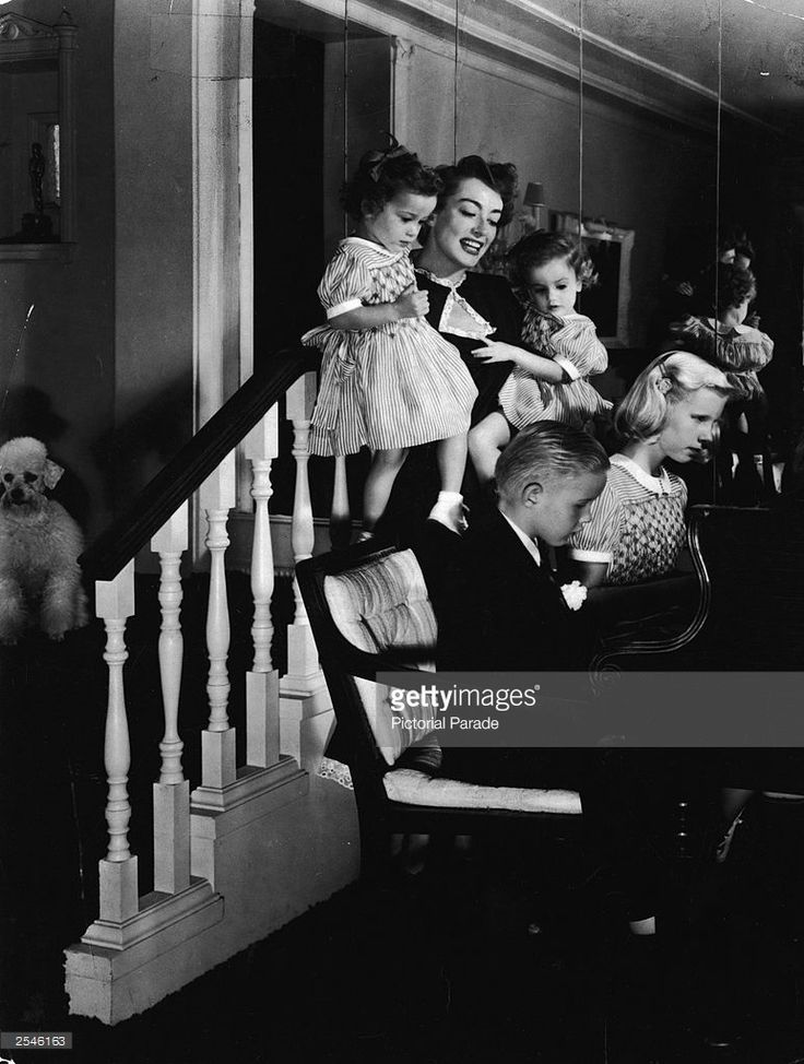 American actor Joan Crawford (1904 - 1977) watches her son Christopher and daughter Christina play the piano while holding her twin daughters Cindy and Cathy, at home in Brentwood, California, 1940s.