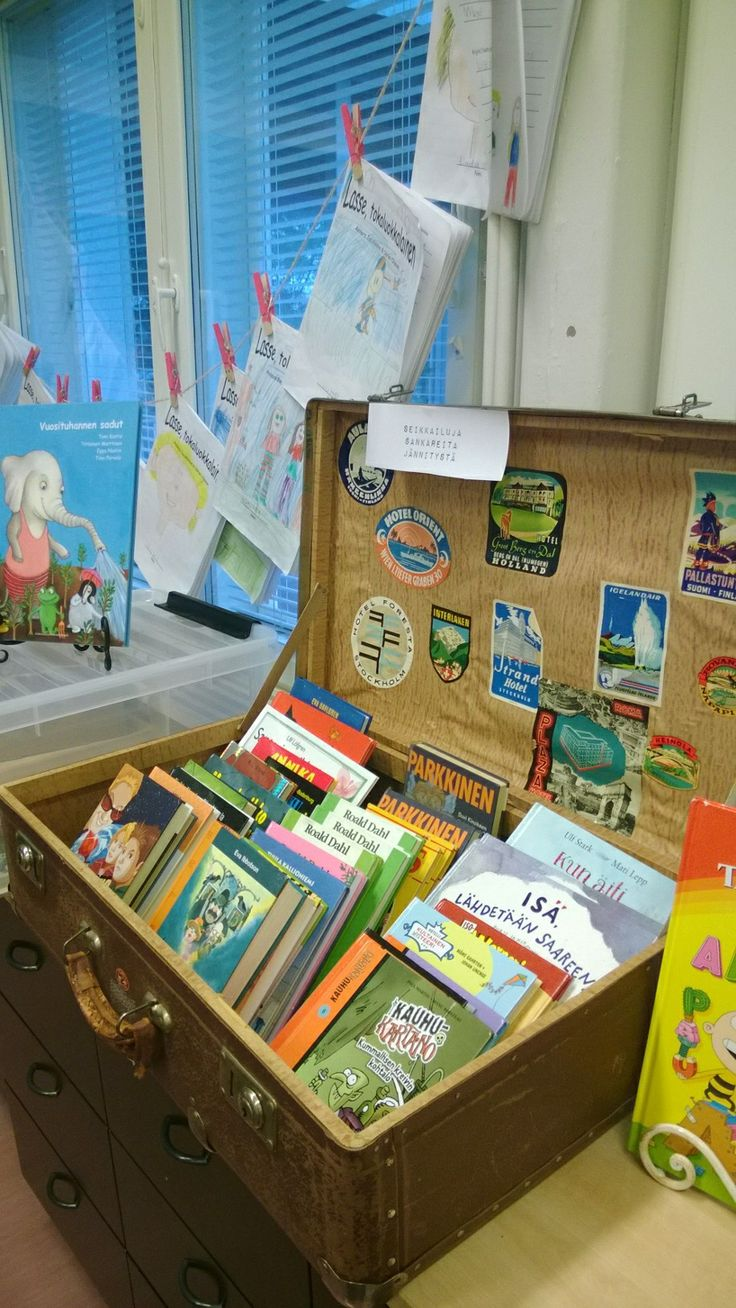 Kirjoja oppilaille luettavaksi, taustalla pyykkinarussa tokaluokkalaisten kirjakerhotehtäviä.