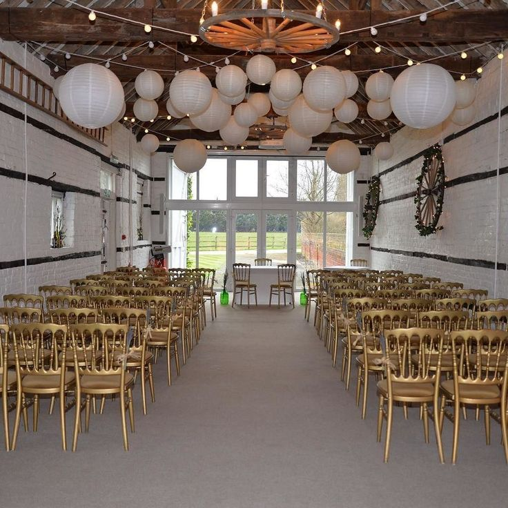 Lillibrooke Manor - Ceremony Room/ small barn. Warm white festoon light canopy with white and ivory lanterns. Lanterns will transform in the evening as the majority are individually lit to have a warm glow.