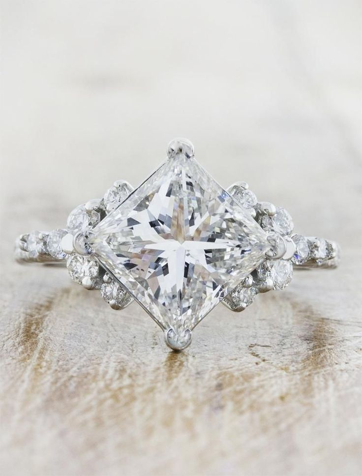 The Loxlynn is a three-stone engagement ring with a glorious cushion cut diamond center stone surrounded by trillions at each side, and accented with a trio of rounds. by Ken & Dana Design. #UniqueEngagementRings