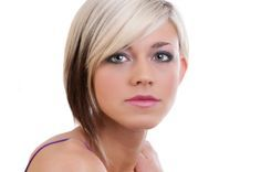 How about a short and layered bob that tapers on one side to a point and has the edgy look of two distinct colors!  A deep side part separates the two sides and long side swept bangs have a sultry look. The top half is bleach blonde mostly absent of pigment. The bottom half is brown with some streaks of blonde sprinkled about. A tail with the bleached shade dangles at the neck. More on Two Tone Asymmetrical Bob