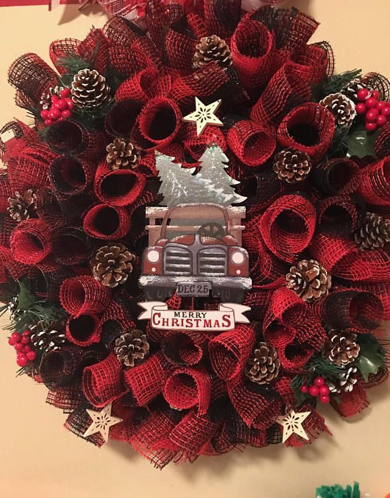 This beautiful country inspired Wreath will warmly great your guests this Holiday season. The wreath measures approximately 24x24x5. The deco mesh used is black and red with a metal truck sign. The pine cones and berrys give it that perfect touch to this country inspired Wreath.
