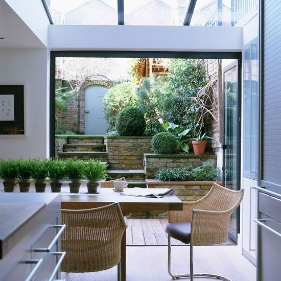 Huge French windows fold back on themselves in this open-plan kitchen/dining room merging the inside and outside space. Conservatory | Contemporary London home | http://www.housetohome.co.uk/house-tour/picture/take-a-tour-of-this-contemporary-london-home/2