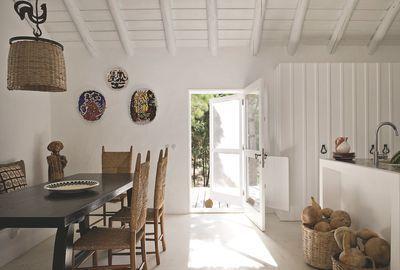 Côté salle à manger, table du designer Olavi Hanninen dans les années 1960, chaises danoises des années 1950. Comme la majorité du mobilier, le lustre provient de la Galerie Saint-Jacques que les décorateurs ont ouverte à Toulouse. Au mur, céramiques de Jean Lurçat, vaisselle Jacques Grange.