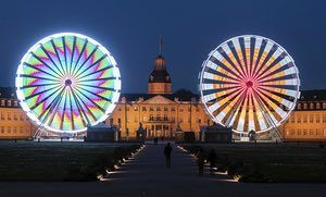 Karlsruhe, Germany. Two ferris wheels on display in front of the castle. The display is in recognition of Karl Drais who was born in the city on 29 April 1785 and invented the running machine, a predecessor to the bicycle