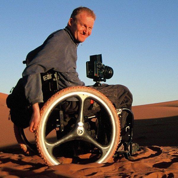 Em cadeira de rodas adaptada, David Constantine visita países em desenvolvimento e comunidades que lutam para se recuperar de conflitos.