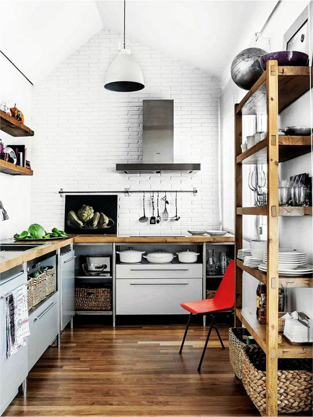 loft kitchen, open shelves, wood floors, wood countertops, white walls, hanging rod for utensils pared de ladrillo
