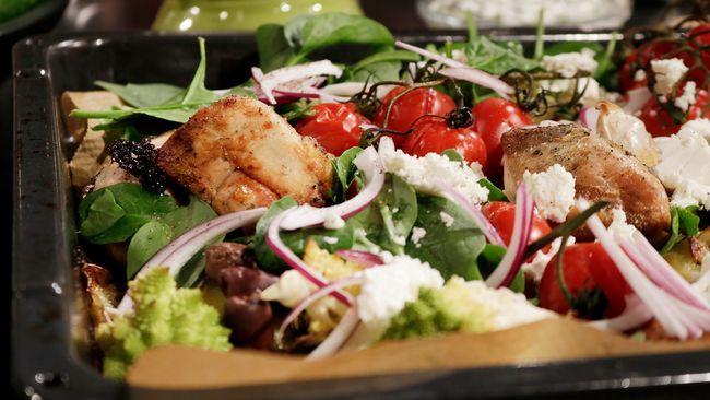 Ugnsplåt med kyckling, tomater, gröna blad och små tomater.